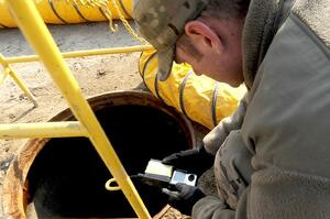 Worker crouching over an open manhole holding a gas monitor