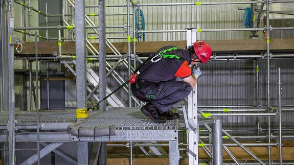 Man wearing a harness and hard hat crouching on the edge of a platform, doing Leading edge fall protection training