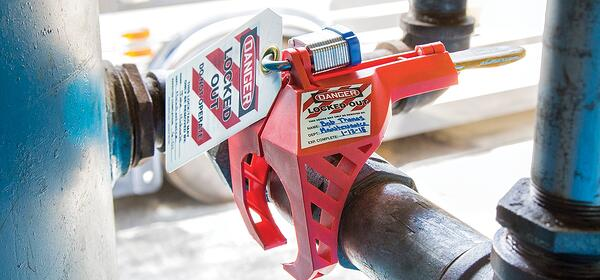 LOTO lock and tag affixed to a lockout-tagout device attached to a pipe valve