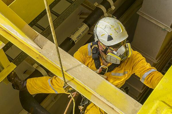worker suspended next to a metal beam, wearing yellow coveralls, a white hard hat, and a full-face respirator mask