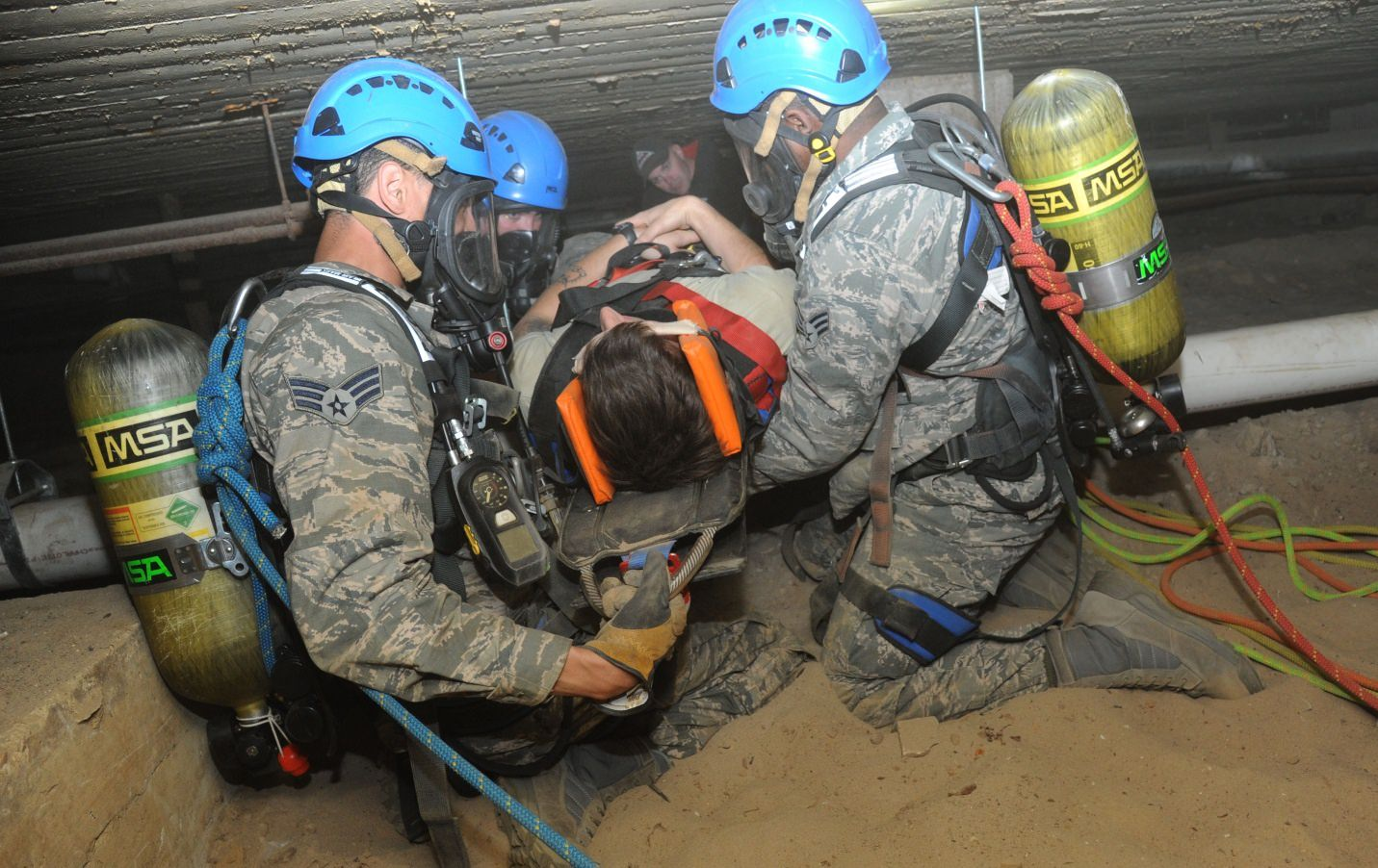 Rescue team pulling a person out of a confined space on a backboard