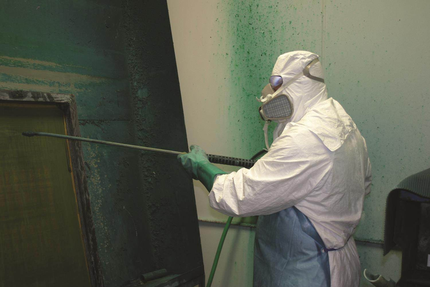 worker wearing disposable white coveralls holding a pressure washer wand