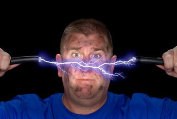 man holding electrified cable that is split in the middle with electricity arcing out of it