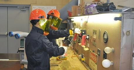 workers wearing hard hats, faceshields, coveralls, and protective gloves doing lockout-tagout training in front of a panel of gauges and switches