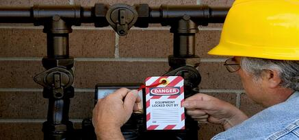 Man standing in front of pipes securing a lockout tag to a valve