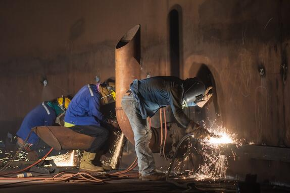 Welders in a dimly lit tunnel welding large pipes