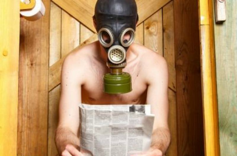 Man sitting shirtless in front of a wooden door holding a newspaper and wearing a gas mask