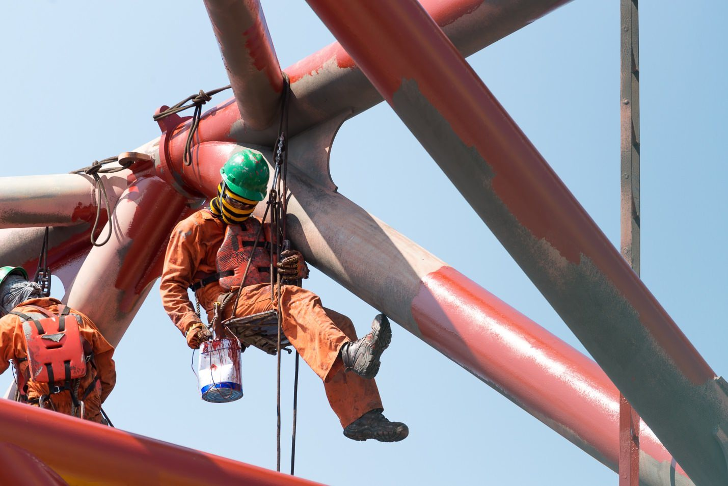 Worker wearing coveralls, hard hat, boots, and gloves suspended next to metal bridge structure