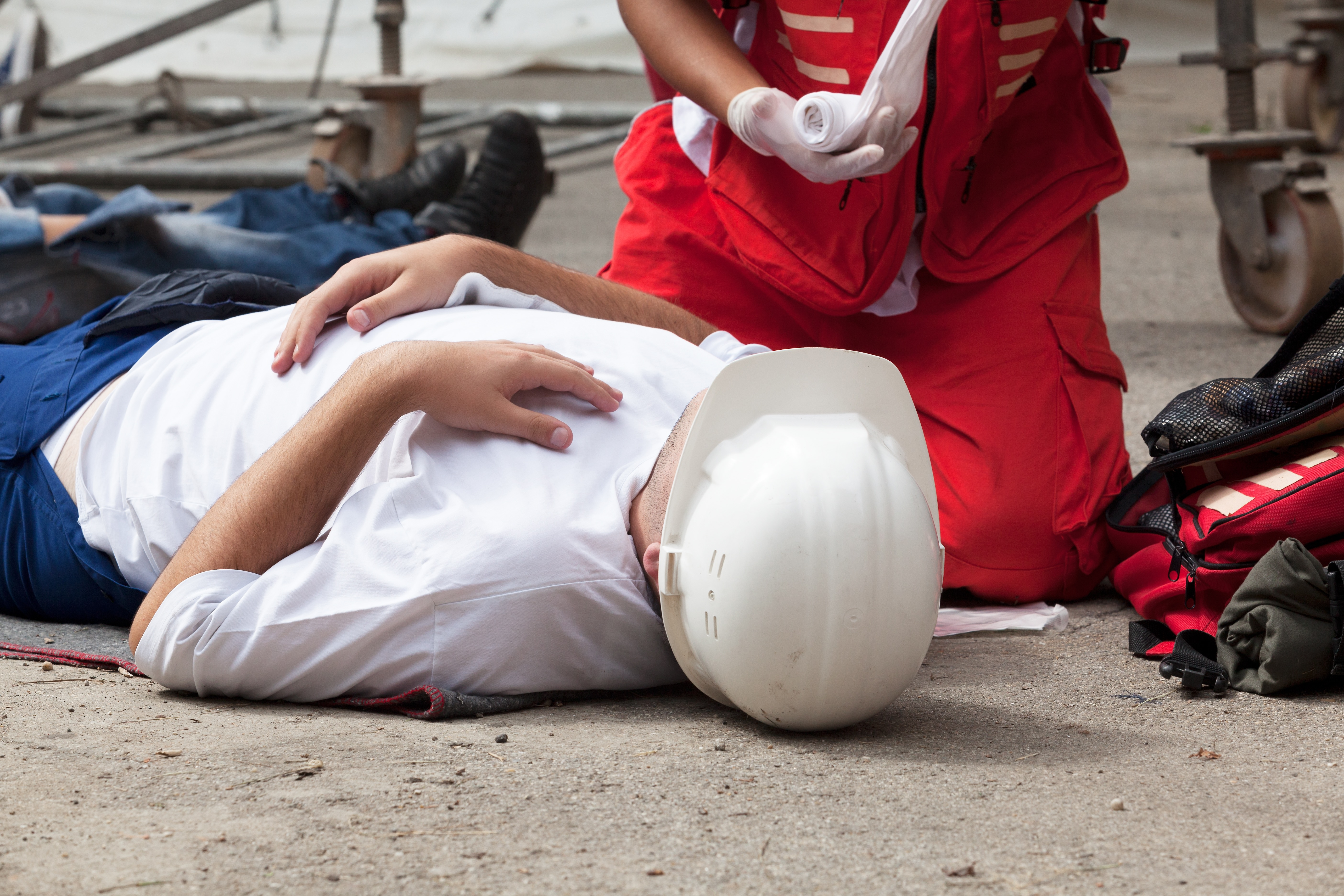 Worker lying on the ground while a First Aid responder kneels next to him unrolling gauze
