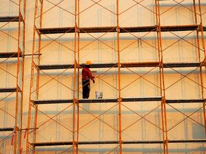 Man standing on scaffolding next to a tall building