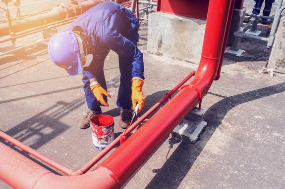 worker wearing coveralls, hard hat, gloves, and disposable respirator mask painting a large pipe red
