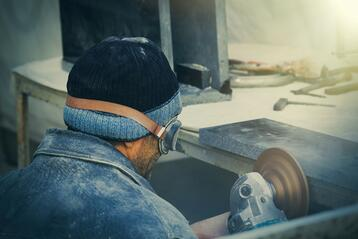 Worker crouched at a work bench using a grinding tool to smooth a board. Dust covers the worker and the bench. Protect workers from silica exposure.