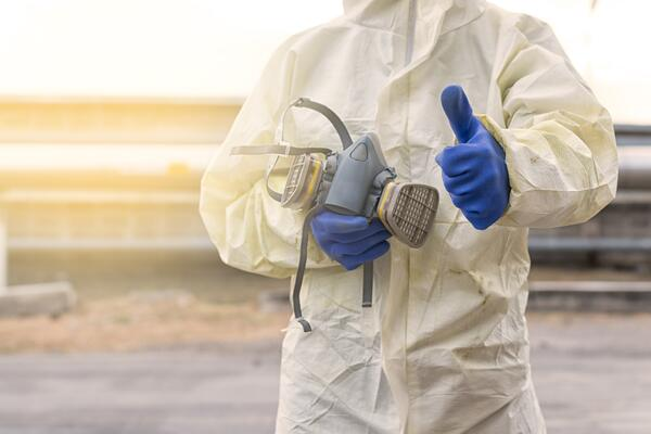 worker wearing white coveralls and blue chemical gloves holding a respirator mask