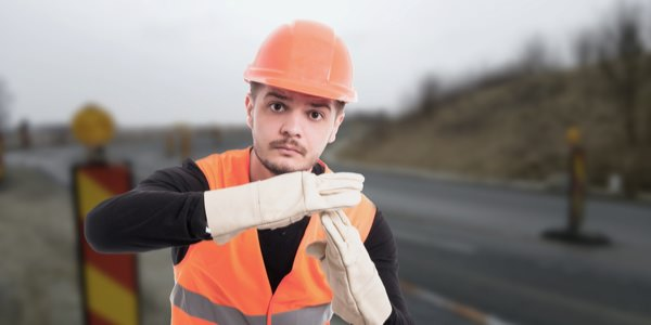 "man wearing a safety vest and hard hat holding his hands up to signal ""stop"""