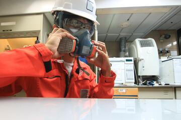 worker wearing orange coveralls, white hard hat, safety glasses, and donning a respirator mask