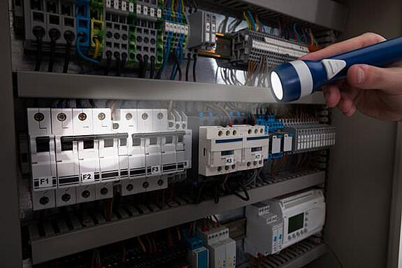 technician using a flashlight on an electrical panel