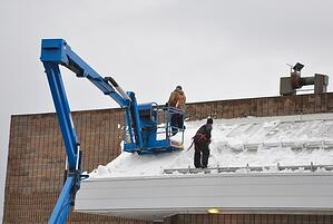 workers in bucket snow on roof fall protection